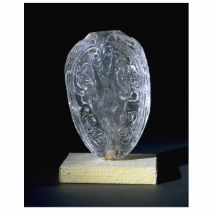 This piece was made between 1000 and 1050. This fine rock crystal piece appears to have been a container. Its complex shape can be seen as the body of a fish. Two convex faces are joined at an angle along the sides, which taper gently towards the base, or tail. However, the fish shape does not continue at the top, where the angled sides broaden out into shoulders. At the centre, these form a collar around the mouth of the hollowed out interior. Another hole was later drilled into the bottom to allow for a mount.