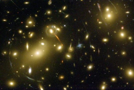 "A massive cluster of galaxies called Abell 2218, some 2 billion light-years from Earth. This ""hefty"" cluster was one of three that Dr. Babul had used when he first proposed the distortions in the images of more distance galaxies by gravity of the cluster can be used to probe the physics of the matter in the cluster."