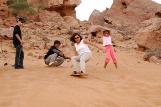 Naznin, Arif's high school sweetheart,  taking on a sandboarding challenge on a desert dune in Dubai