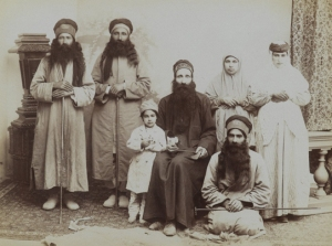 A Family of Dervishes. Possibly Antoin Sevruguin (Armenian-Georgian, 1830s–1933). Iran, late 19th–early 20th century. Silver albumen photograph. Brooklyn Museum, Purchase gift of Leona Soudavar in memory of Ahmad Soudavar, 1997.3.139. A Sufi's attributes and clothing indicate the mystical order to which he or she belongs and may also suggest rank and status within that order. Here, the patriarch's black robe emphasizes his authority. The varied styles of the hats further delineated positions within the group. The central seated figure holds a tabar, a small ceremonial axe, while each of the remaining men holds a walking staff, another iconic Sufi attribute. The extremely long beards of the male members identify this group as part of the Ahl-i Haqq order of Sufis, whose practices are guarded with extreme secrecy. The photograph may have been taken by Antoin Sevruguin, who served at the court of the Qajar ruler Nasir al-Din Shah in the latter nineteenth century and who is known for his portraits of Iranian landscapes and subjects.