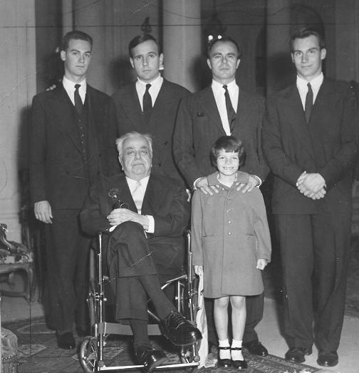 The late 48th Ismaili Imam, His Highness the Aga Khan, seated on a wheelchair with members of his family with his successor, the present Imam, Prince Karim Aga Khan, standing at extreme right. Others in the photo (l to r), grandson Prince Amyn Muhammad, and the late Imams two sons, the late Prince Sadruddin and Prince Aly Khan, who is seen holding his daughter Princes Yasmin Aga Khan Photo: Zul Khoja Collection, Ottawa.