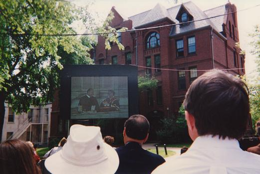 "May 26, 1996: An audience at Brown Univeristy's ""Green"" watches a live telecast from the Meeting House of the First Baptist Church where the Aga Khan delivered the Baccalaureate Address to graduating class. Photo: Abdulmalik Merchant"