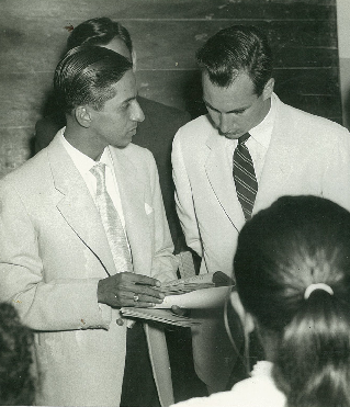 Lourenço Marques, 1958: His Highness the Aga Khan, direct descendant of the Prophet Muhammad (s.a.s.) and current 49th hereditary Imam of the Shia Ismaili Muslims is seen taking a keen interest as Alwaez Jehangir explains the Gujarati history texts that were used to impart religious education to Ismaili youth in Mozambique.