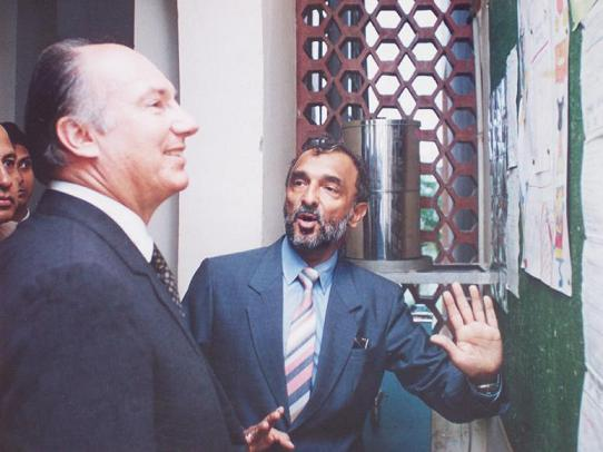 This visit to the Aga Khan School in Dhaka took place during Mawlana Hazar Imam's four day stay in Bangladesh in 1993. During the school visit Hazar Imam was accompanied by a Government Minister, The President of the Council, school board members. In this photo, Zul Khoja, the principal of the school from 1992-1994 is seen showing a curricular activity implemented to introduce creative and critical thinking among the students. Mawlana Hazar Imam took immense pride in this activity, known as the Mind Benders Club, and turned to his guests to explain the accomplishments in his school. Zul notes that when Mawlana Hazar Imam introduced him o the guests, it was done with a