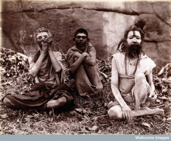 Two men and a boy sitting cross-legged on the ground surrounded by leaves; their faces are painted white and one of them appears to be smoking a pipe: Bombay at the time of the 1896/97 plague. Photo Credit: Wellcome Library, London. Wellcome Images.