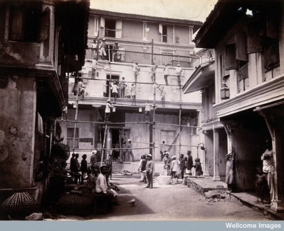 plague house being whitewashed by men standing on scaffold Credit: Wellcome Library, London. Wellcome Images images@wellcome.ac.uk http://wellcomeimages.org A plague house being whitewashed by men standing on scaffolding in Bombay. Photograph, 1896. Photo Credit: Credit: Wellcome Library, London. Wellcome Images