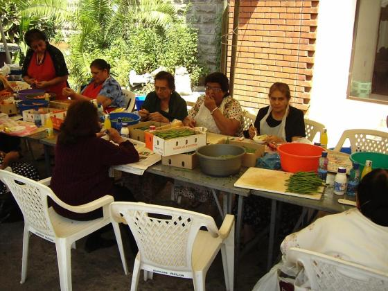 Volunteers hard at work, with some taking a deserved break from chopping and peeling vegetables.
