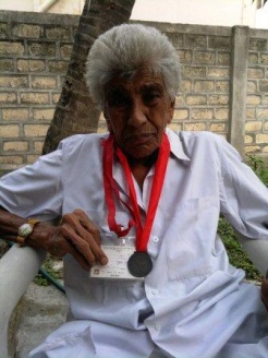 Long serving Ismaili, 77 year old Gulamhusen Alibhai Jamani of Mahuva, India, with a  medal that was presented him during Volunteer Day.
