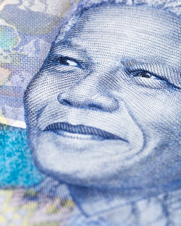 Extreme close-up of a detail of a new South African Hundred Rand banknote, featuring an engraving of the face of iconic statesman Nelson Mandela, giving his trademark smile. South African wildlife and African designs form the watermarked background. Photo: Istockphoto> Copyright.