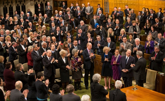 "His Highness the Aga Khan is applauded by the Prime Minister, Members of the House, as well as other distinguished visitors as he arrives  in the House of Commons on Thursday, February 27, 2014 to deliver a rare address - the first by a faith leader in 75 years. The Ottawa Citizen published a similar photo on its front page of Friday February 28, giving it the title ""In Divine Company."" Alongside the Ismaili Imam are his daughter Princess Zahra and the Prime Minister's wife, Laureen Harper. Others in the photo, in rows adjacent to Mrs. Harper (l to r) -- 1st row: The Aga Khan's younger brother, Prince Amyn Muhammad Aga Khan, Chief Justice of the Supreme Court of Canada, The Right Honourable Beverly McLachlin, Former Governor General of Canada, The Right Honourable Adrienne Clarkson, and renowned Canadian author, intellectual and philosopher,  John Ralston Saul; 2nd row (l to r). President Malik Talib of the Aga Khan Ismaili Councli for Canada, Prince Hussain Aga Khan, Princess Salwa Aga Khan and her husband Prince Rahim Aga Khan - with both the Princes in the photo being the Aga Khan's children. Photo credit: The Office of the Prime Minister of Canada."