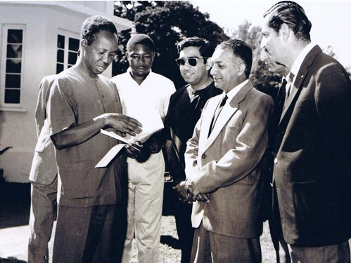 A rare photo of Arusha's Ismaili leaders with Mwalimu Julius Nyerere taken during a community donation in the late 1960's. (L to R) -- The late Tanzanian President Julius Nyerere, Hashim Mbita, press secretary to the president, Akber Natha Hirji, a member of Ismaili regional council, Mukhi Kamrudin Hasham Jessa, Kamadia Madat Vassanji, and Moosa Janmohamed, also a member of the regional council headquartered in Moshi. The photo was taken during at the guest house for the president in Arusha. The donation was for a local community project. Photo credit: www.Juliusnyerere.info