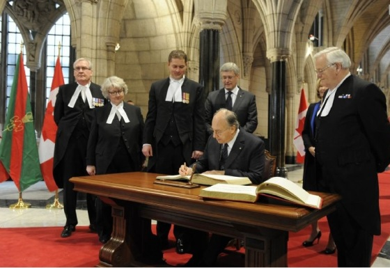 His Highness the Aga Khan signs the visitors books for the House of Commons and the Senate in the Canadian Parliament Rotunda as Prime Minister Stephen Harper, his wife Laureen Harper, The Honourable Andrew Scheer, Speaker of the House of Commons and the Honourable Noël Kinsella, Speaker of the Senate look on. Photo credit: TheIsmaili/Gary Otte.
