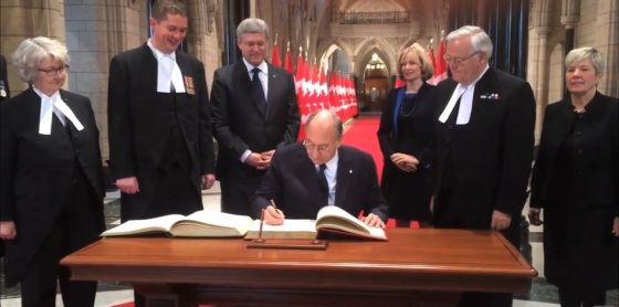 Mawlana Hazar Imam signs the distinguished visitors books for the House of Commons and the Senate in the Canadian Parliament Rotunda as Prime Minister Stephen Harper, his wife Laureen Harper, The Honourable Andrew Scheer, Speaker of the House of Commons and the Honourable Noël Kinsella, Speaker of the Senate, and other individuals look on. Photo: Post Media Clip