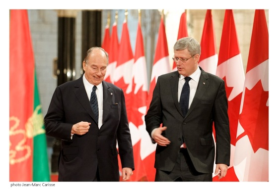 His Highness the Aga Khan and Prime Minister Harper in a conversation as they proceed to the signing ceremony of  the protocol of understanding between the Ismaili Imamat and Canada. They are flanked on either side by the flags of the red and green flags of the Ismaili Imamat and the maple leaf of Canada. Photo: Jean-Marc Carisse. Copyright.