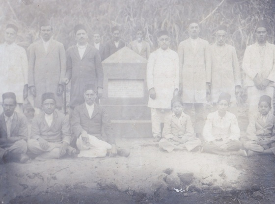 A historical photo showing  members of the Kilosa Ismaili jamat pictured beside the monument to the shaheeds which was built in 1926-27 at the site of the accident . The monument continues to be maintained by the Morogoro Ismaili jamat. From l to r (Seated): Jaffer Ladha, Kassam Dhalla, Meghji Visram, Hassanali Lalji Hirji Mawani, Janmohamed Dharamsi, Gulamali Karim Khakoo; Standing: Bhimji Hamir, Lalji Ladha Vali,  Ladha Nanji, Bandali Haji, Karim Khakoo, Haji Hamir, Razak Kanji Nanji, (Behind the Monument): Abdulrasul Dharamsi, Ladha Mohamed, Rajabali Haji (as identified by my uncle Rai Abdulrasul Meghji Visram). Photo: Sadru Meghji Collection. Copyright.