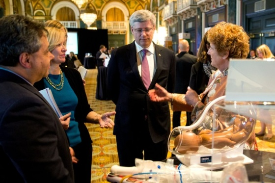 Prime Minister Stephen Harper receiving an explanation about an exhibit displaed at the summit Saving Every Woman, Every Child: Within Arm's. Phooto: The website of the Prime Minister of Canada.