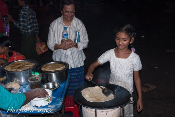 "Nevin Harji looks on as a smiling young Burmese girl prepares hot roti/paratha. Please click on photo for ""Street Foods of South Asia. Photo: Muslim Harji, Montreal, PQ, Canada. Copyright."