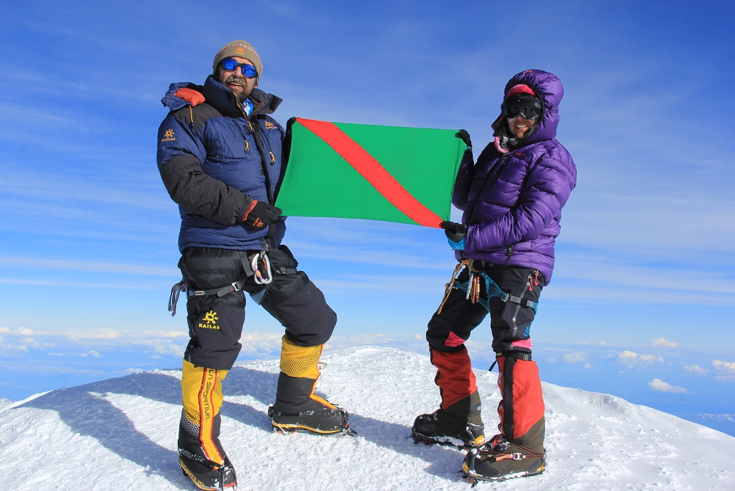 """Mirza Ali and his sister Samina Baig hoist the Ismaili Imamat Flag after reaching the summit of North America's highest mountain, Mt. McKinley, in Alaska, on June 28, 2014. Their goal is to reach all the """"Seven Summits"""", and with this latest conquest only one remains to be peaked. Photo: Malik Mirza/Samina Baig."""