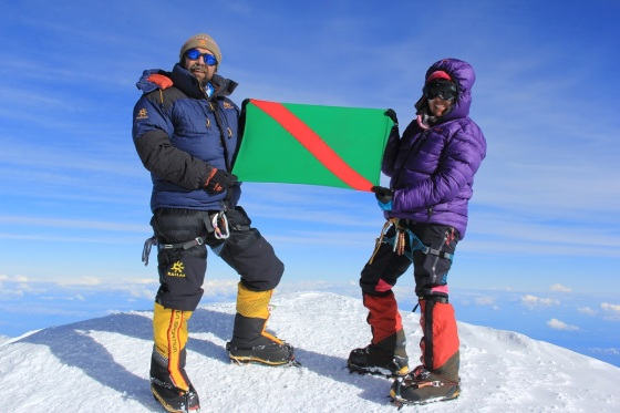 "Mirza Ali and his sister Samina Baig hoist the Ismaili Imamat Flag after reaching the summit of North America's highest mountain, Mt. McKinley, in Alaska, on June 28, 2014. Their goal is to reach all the ""Seven Summits"", and with this latest conquest only one remains to be peaked. Photo: Malik Mirza/Samina Baig."