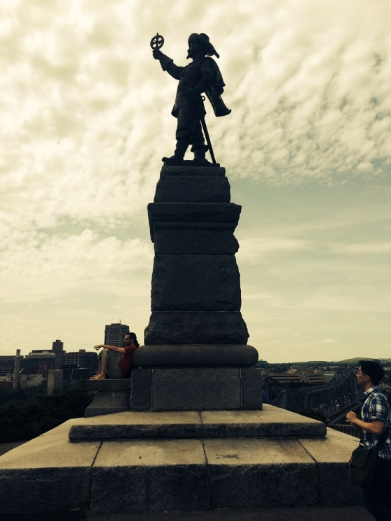 A statue of French explorer Samuel de Champlain at Nepean Point in Ottawa. The explorer is  seen holding his famous astrolabe upsidedown. Nepean Point is a hill in Ottawa, Ontario, Canada, overlooking the Ottawa River, Parliament, the Canadian Museum of Civilization, and other features of downtown Ottawa and Gatineau. It is located between the National Gallery of Canada and Alexandra Bridge. The sculpture was made by Hamilton MacCarthy in 1915. Photo: Malik Merchant, Copyright.