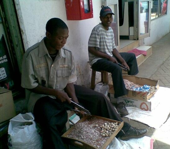 Sopari cutters sit outside the paan shop totally engrossed in cutting soparis with a commercial sopari cutters. Photo: Farida Keshavjee.