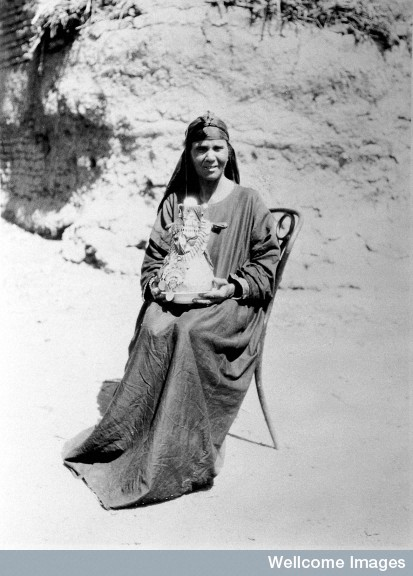 A midwife in Upper Egypt holding a kulleh pot. Also known as the goollah, it is a porous water-jar of sun-dried Nile mud. Photo Credit: Winifred S. Blackman/ Wellcome Library Image, London.