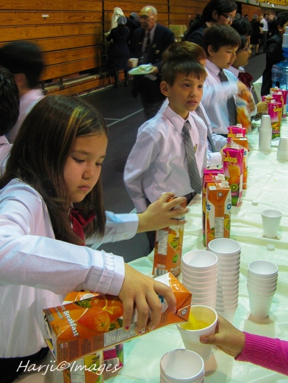 Junior Ismaili Volunteers serving juice at a jamati jaman (feast). Please click on photo for photo essay. Photo: Muslim Harji.