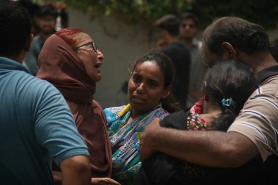 KARACHI, PAKISTAN - MAY 13: Relatives of injured and killed cry and wait outside a hospital following a gun attack on a bus carrying members of Ismaili Shia community, in Karachi, Pakistan, 13 May 2015 that killed at least 45 people including over a dozen women and injuring more than 14 people. (Photo by Sabir Mazhar/Anadolu Agency/Getty Images)