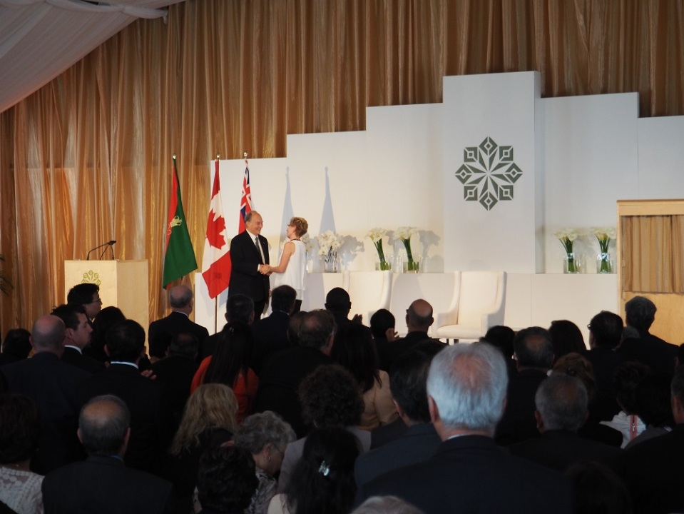 Mwlana Hazar Imam receives a standing ovation as he is congratulated by Premier Kathleen Wynne after the completion of his speech at the opening of the Aga Khan Park on May 25, 2015. Photo: Simerg/Malik Merchant. Copyright.