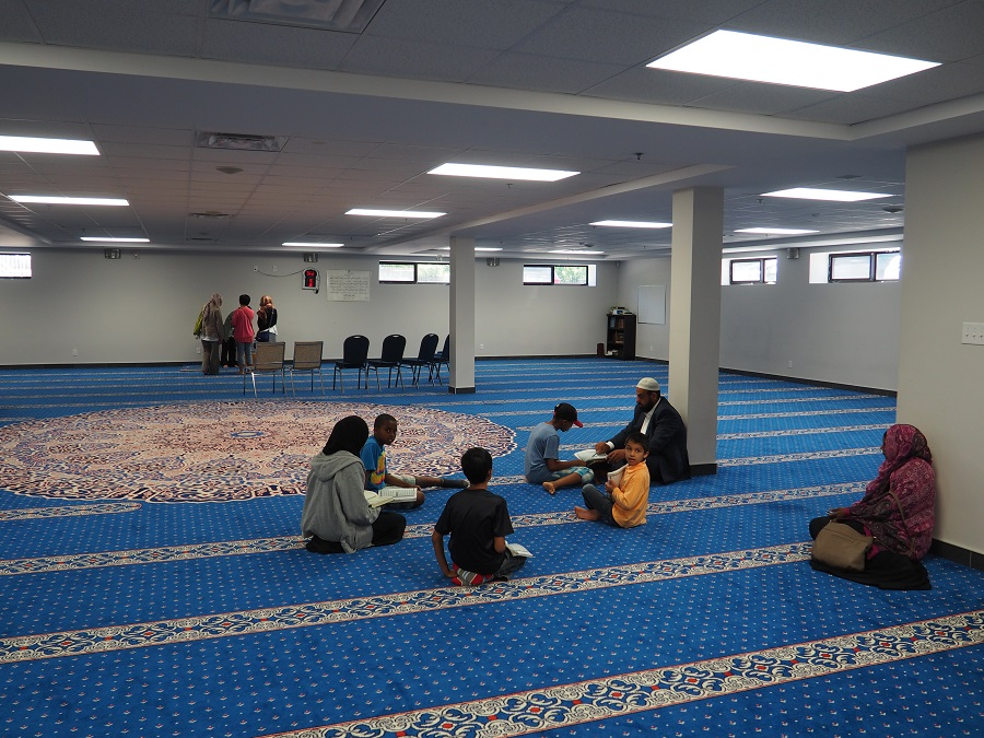 The space in the basement currently used for prayers while  the main large hall upstairs gets its finishing touches. Here children are seen learning the Holy Qura'n from their Qura'nic teacher, brother Mehdi. Photo: Simerg/Malik Merchant.