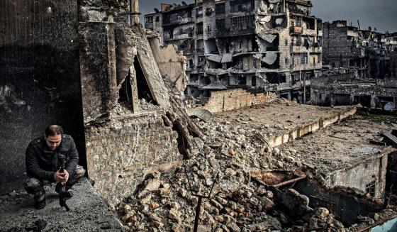 A sergeant in Lewa Salaheddin, a Kurdish battalion of the Free Syrian Army, sits in front of a block of destroyed buildings in Aleppo, Syria on December 6, 2012. It's more than three years since the fight for Aleppo began. By late 2012, parts of the city were already in ruins. Patrick Tombola/laif/Redux