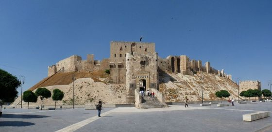 The Citadel of Aleppo is a large medieval fortified palace in the centre of the old city of Aleppo, northern Syria. It is considered to be one of the oldest and largest castles in the world. Usage of the Citadel hill dates back at least to the middle of the 3rd millennium BC. Subsequently occupied by many civilizations including the Greeks, Byzantines, Ayyubids and Mamluks, the majority of the construction as it stands today is thought to originate from the Ayyubid period. An extensive conservation work has taken place in the 2000s by the Aga Khan Trust for Culture in collaboration with Aleppo Archeological Society. Dominating the city, the Citadel is part of the Ancient City of Aleppo, a UNESCO World Heritage Site since 1986. The Citadel has received significant damage in the ongoing Syrian Civil War. Photo and caption: Wikipedia.