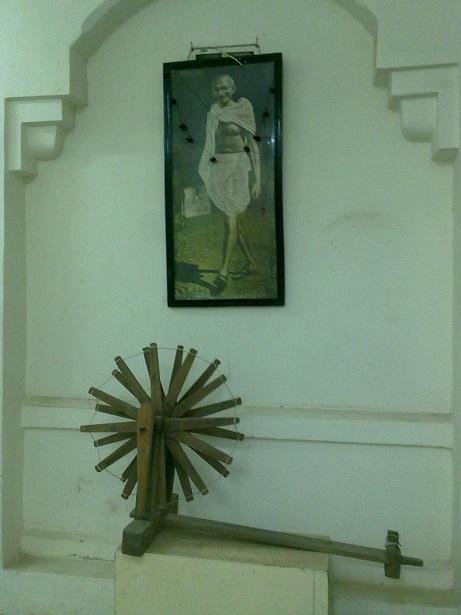 A replica of Nazarali Bapa's spinning wheel below Mahatma Gandhi's portrait at the Amreli Museum. The original wheel was designed to honour Gandhi's visit to Saurashtra. Photo: Khushid Makani Collection.