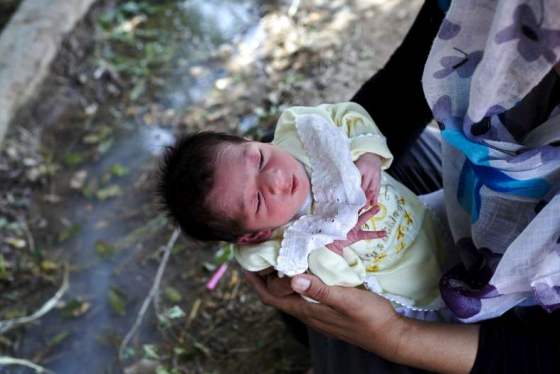 Ten-day-old Hawler is held by her mother, a Syrian Kurd who named her after a region in Kurdistan. The family's makeshift campsite in the park is situated next to a mosquite ridden pool of water. Photo: UNHCR/S. Baldwin. Copyright.