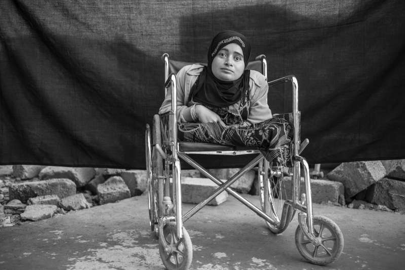 Alia sits in her wheelchair in Domiz refugee camp in the Kurdistan Region of Iraq. The 24-year-old was living with her family in Daraa, Syria, when fighting forced them to flee their home. Confined to the wheelchair and blind in both eyes, Alia says she was terrified by what was happening around her. 'Men in uniforms came and killed our cow. They fought outside our house and there were many dead soldiers. I cried and cried,' she says. Alia says the only important thing that she brought with her 'is my soul, nothing more – nothing material.' When asked about her wheelchair, she seems surprised, saying she considers it an extension of her body, not an object. Photo UNHCR/B.Sokol. Copyright.