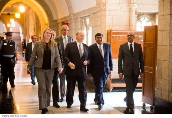 His Highness the Aga Khan walks happily in the corridor of the Parliament Building following his meeting with Prime Minister Justin Trudeau on Tuesday May 17, 2016. He is accompanied, among others, by Ismaili leaders Shafik Sachedina and the President of the Aga Khan Council for Canada, Malik Talib. Photo: Jean-Marc Carisse. Copyright.