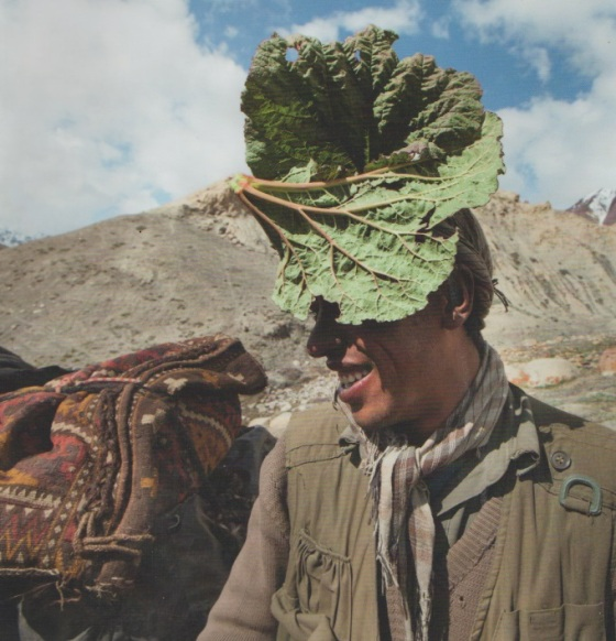 Using a wild rhubarb leaf as his parasol, a traveller shields his face against the strong sun of the high Pamir Mountains in Afghanistan. Photo/Caption: With Our Own Hands