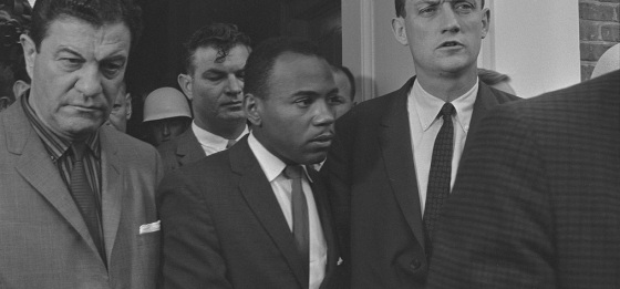 Photograph shows James Meredith walking on the campus of the University of Mississippi, accompanied by U.S. marshals. LOC photo reproduced in Simerg