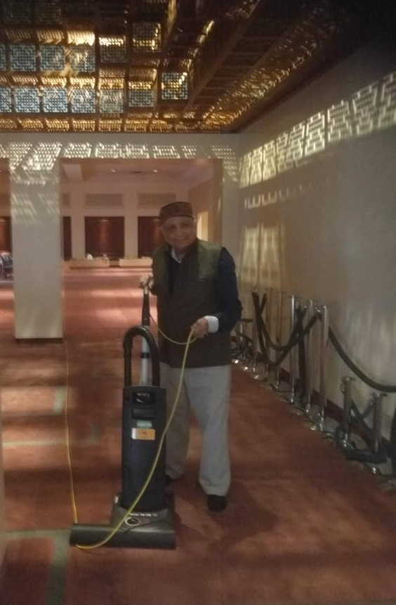 Sadru Velji vacuuming Ismaili Jamatkhana Photo: © Sadruddin Velji Family Collection.
